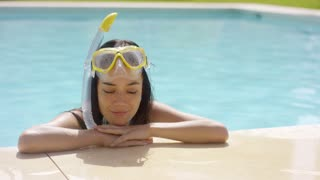 Woman in snorkel and goggles rests by pool and smiles to herself while standing in the water