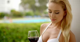 Woman in White Bikini Holding Glass of Red Wine