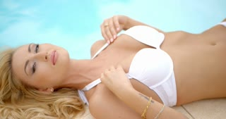 Woman in White Bikini Lying Next to Swimming Pool