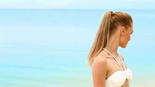 Woman in white bikini relaxing on the beach