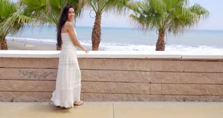 Woman in White Dress by Wall Overlooking Beach