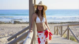 Woman in white swim suit and straw hat stands on wood boardwalk near beach and ocean