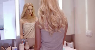 Woman Looking at Herself on the Bathroom Mirror