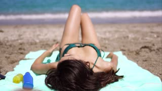 Woman lying facing away from the camera suntanning on a towel on a tropical beach in summer sun on her annual vacation