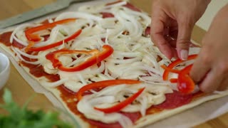 Woman make a tasty traditional homemade Italian pizza with tomato paste salami mushroom and onion topping as she carefully places sliced fresh red bell pepper on top close up of the food.