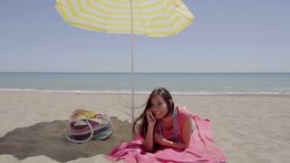 Woman on phone call at beach under umbrella