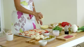Woman preparing a homemade salami and mushroom pizza in the kitchen putting grated cheese on top as she stands at a wooden table close up view of the surface and ingredients.