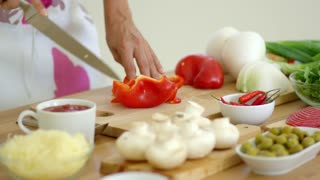 Woman preparing dinner at home in the kitchen chopping fresh ingredients on a wooden counter as she slices a fresh red bell pepper with a knife.