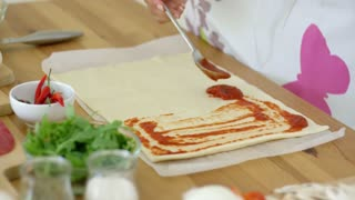Woman preparing traditional homemade Italian pizza spreading tomato chili paste on to freshly rolled dough for the base