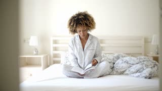 Woman Reading A Book On Bed