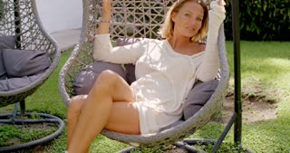 Woman Relaxing in Wicker Chair Outdoors in Garden