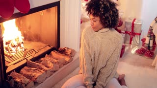 Woman seated by fireplace and holiday setting and wearing warm woolen sweater and white leggings. She has Christmas tree behind her back.