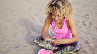 Woman sitting at beach listening to music