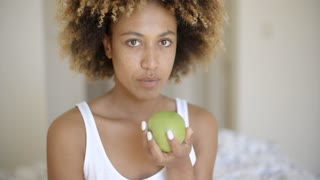Woman Sitting On Bed And Eating Apple