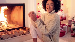 Woman smiles at camera while wearing sweater and seated in front of a raging fireplace and plastic white christmas tree