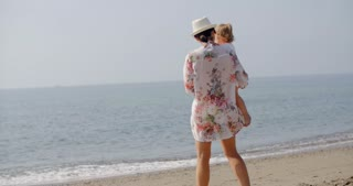 Woman Standing on Beach Holding Small Child