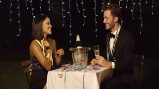 Woman teases her dinner date with ribbon across table while sharing champagne