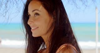 Woman Under a Beach Umbrella Smiling at Camera