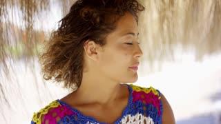 Woman under thatch beach umbrella