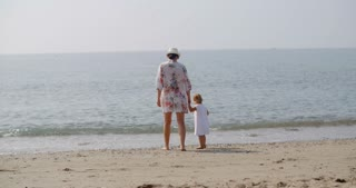 Woman Walking Hand in Hand with Child on Beach