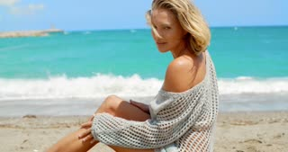 Woman Wearing Grey Sweater Sitting on Sandy Beach