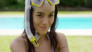 Woman wearing snorkel and swim goggles sits in the grass beside an empty pool