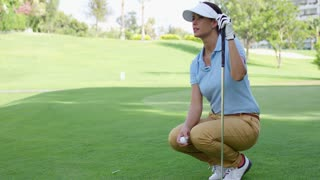 Woman wearing white visor and blue polo shirt squats on golf course while holding club and ball