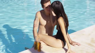 Woman with bottled beverage sits on side of pool as tattooed boyfriend places one hand on either side of her