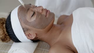 Woman With Clay Facial Mask In Spa