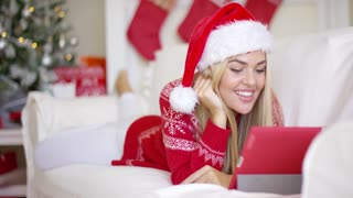 Yound smiling beautiful girl video chatting with friends over touchpad while lying on couch. She wearing Santa Claus hat on her head, red warm winter sweater with xmas pattern.