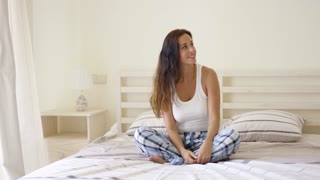 Young adult woman in plaid pajama pants looking sideways toward window curtains while seated on bed