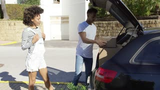 Young African American couple moving home working as a team packing boxes into their car parked on the street