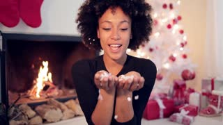 Young african american woman with big afro haircut blowing white confetti off her hands as she celebrates Christmas at home in front of a burning fireplace and beautifully decorated white Xmas tree.