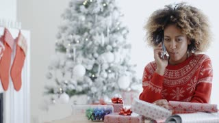 Young African woman wrapping gifts at Christmas