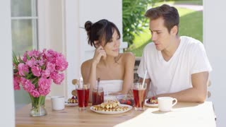 Young attractive couple drinking iced tea together at table with breakfast waffles coffee fruit and pink flower vase