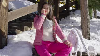 Young beautiful asian woman relaxing on whe wooden bench in snowy winter conditions. She wearing pink ski clothes. Smiling to the camera.