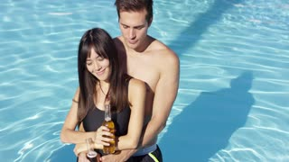 Young beautiful mixed race couple standing and holding in the swimming pool. They drink refreshing cold beer
