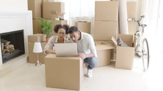 Young black couple moving into their new home sit beside unpacked boxes and look at laptop