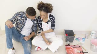 Young black couple sit and listen to music after a long day of painting