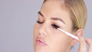 Young blond woman applying mascara to her eyelashes with a brush in a beauty and makeup concept close up cropped face portrait on grey