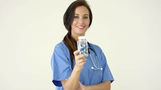 Young brown haired doctor in scrubs holds bottle towards camera against a light colored background