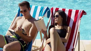 Young Caucasian and Asian male and female couple in sunglasses reading books on deck chairs at the swimming pool