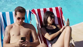 Young Caucasian and Asian male and female couple in sunglasses reading or checking messages on their cell phones while in deck chairs at the swimming pool.