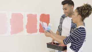 Young couple checking paint swatches on cards against painted pages on the wall as they try to decide on the colors for their redecoration of the house.