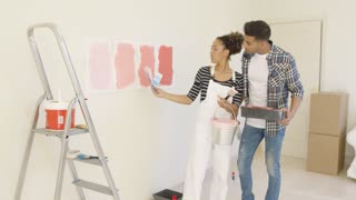 Young Couple Discussing Shades Of Paint Color Together As They Renovate Their Apartment Standing Looking At