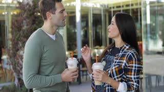Young couple drinking takeaway beverages standing side by side enjoying a quiet chat outdoors in an urban street