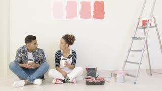 Young couple enjoying a takeaway coffee together sitting on the floor while renovating and painting their home