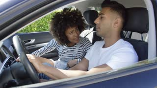 Young couple having a serious talk in a car with focus to the woman staring intently at her husband or boyfriend as he sits behind the wheel viewed through the open window.
