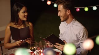 Young couple laughing as they go through the menu at a restaurant ordering their meal with colorful party lights behind them