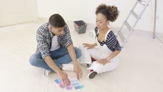 Young couple looking at paint swatches for decorating their new home sitting on the floor in the living room